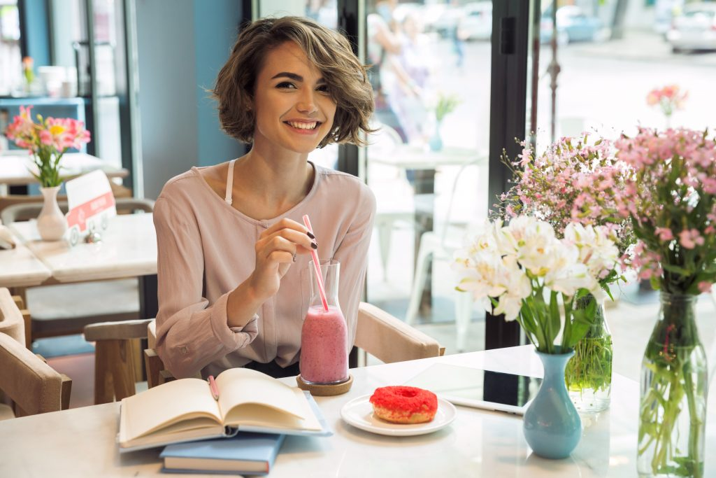 Smiling pretty girl drinking smoothie with a straw while studying with books in a cafe